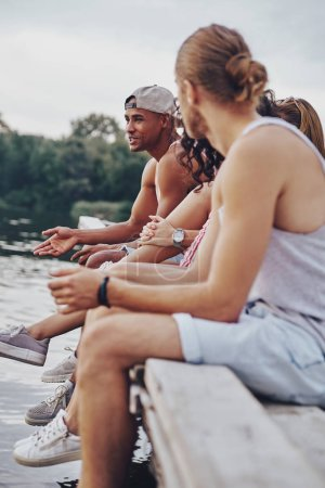 best friends sitting on wooden pier at lake