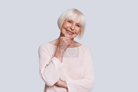 happy caucasian grandmother in light sweater and short grey hair posing at grey background in studio and holding hand at chin