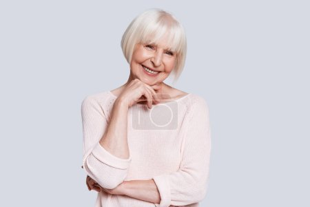 happy caucasian woman in light sweater and short grey hair posing at grey background in studio and holding hand at chin