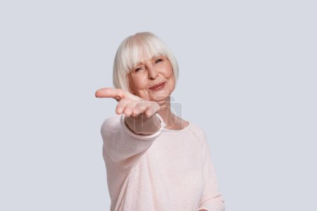 smiling caucasian woman in light sweater and short grey hair posing at grey background in studio, stretching arm to camera
