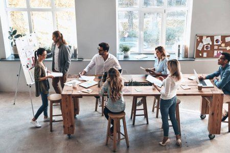 Photo for Business colleagues brainstorming in modern office at wooden table - Royalty Free Image