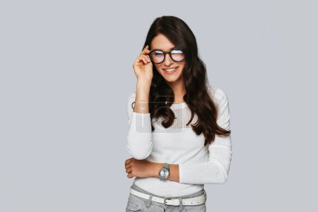 Photo for Confident and beautiful young woman adjusting eyewear and smiling while standing against grey background - Royalty Free Image