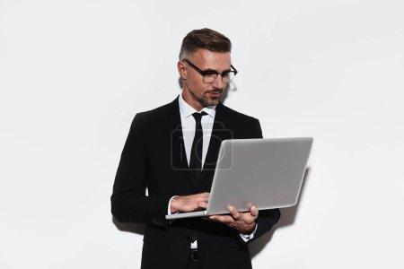 Photo pour Homme d'affaires beau à l'aide d'ordinateur portable, debout sur fond blanc - image libre de droit
