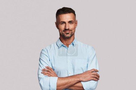 Photo pour Irrésistible homme regardant la caméra et souriant tout en se tenant debout sur fond gris avec les bras croisés - image libre de droit