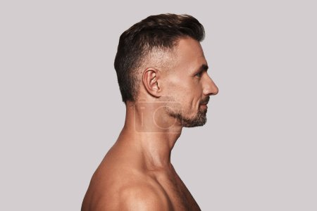 Photo for Shirtless man, Side view of good looking young man standing against grey background - Royalty Free Image