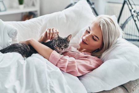 Photo pour Jolie jeune femme jouant avec son chat et souriant tout en étant couché au lit à la maison - image libre de droit