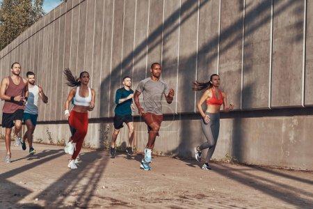 Photo pour Pleine longueur de personnes en vêtements de sport jogging pendant l'exercice sur le trottoir à l'extérieur - image libre de droit