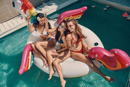 Photo pour Vue du dessus des jeunes femmes attrayantes en maillots de bain souriant et buvant du champagne tout en flottant sur la licorne gonflable dans la piscine à l'extérieur - image libre de droit