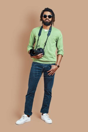 Photo for Full length of young African photographer in casual clothing looking at camera while standing against brown background - Royalty Free Image