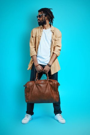 Photo for Full length of young African man in casual wear carrying leather bag and looking away while standing against blue background - Royalty Free Image