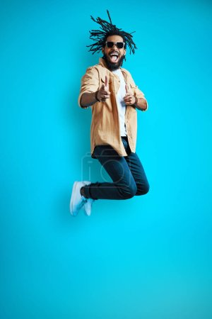 Photo for Full length of cheerful Young African man in casual wear shouting and gesturing while hovering against blue background - Royalty Free Image
