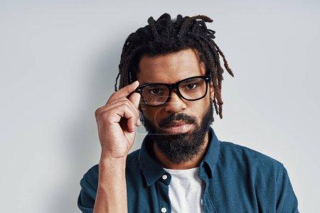 Photo pour Charmant jeune homme africain en tenue décontractée regardant la caméra et ajustant les lunettes tout en se tenant debout sur fond gris - image libre de droit
