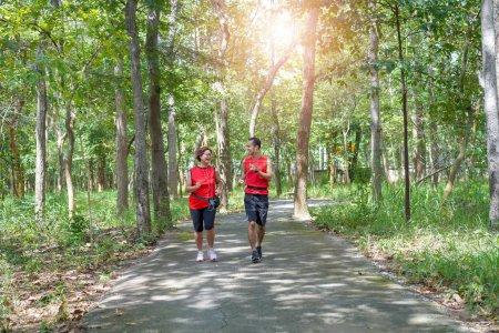 Photo pour Happy senior asiatique femme avec homme ou entraîneur personnel jogging courir dans le parc, Soins aux personnes âgées exercice sport activité concept - image libre de droit