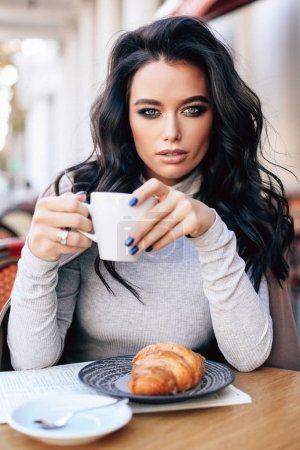 Photo for Fashion outdoor photo of beautiful woman with dark hair in elegant clothes posing in the street cafe - Royalty Free Image