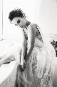 """Постер, картина, фотообои """"Мода интерьер фото красивая женщина невеста с темными волосами в роскошное свадебное платье позирует в ванной в ванной комнате"""""""
