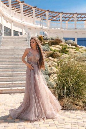 Photo pour Mode photo extérieure de belle femme avec de longs cheveux foncés en robe de soirée luxueuse - image libre de droit