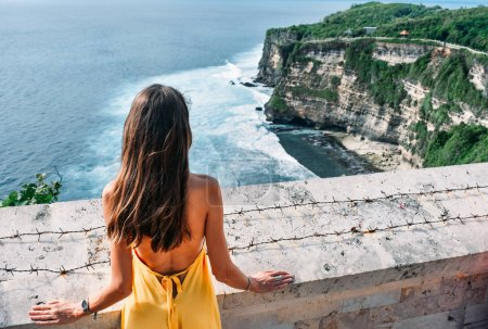 Asienreisen. schöne Frau mit dunklen Haaren in elegantem gelben Kleid mit einem Panoramablick auf den Ozean