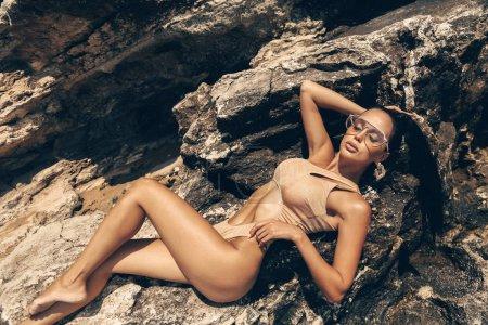Photo pour Photo mode extérieure d'une belle femme sexy aux cheveux foncés en maillot de bain élégant posant sur la plage d'été - image libre de droit