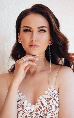 Photo pour Photo studio de mode de belle femme aux cheveux foncés en robe luxueuse avec des bijoux - image libre de droit