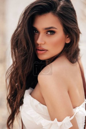 Photo for Fashion photo of beautiful woman with dark hair in elegant beach clothes relaxing on the summer beach - Royalty Free Image
