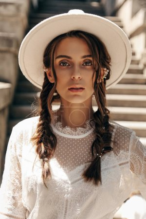Photo for Fashion outdoor photo of beautiful woman with dark hair in elegant white dress and hat posing at on the stairs - Royalty Free Image