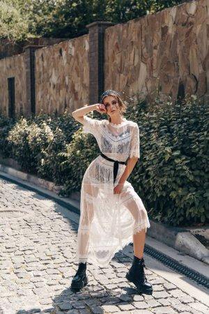 Photo pour Photo extérieure de mode de belle femme aux cheveux foncés dans une élégante robe blanche et accessoires - image libre de droit