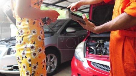 Photo pour Client donnant des clés de voiture au mécanicien de garage - image libre de droit