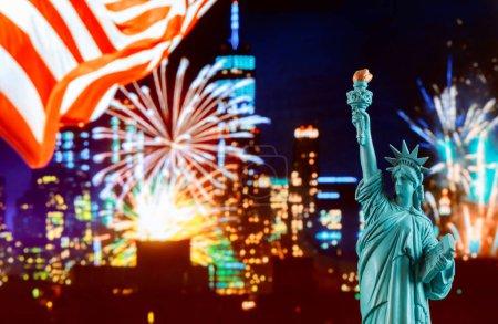 Manhattan skyline at night and Statue of Liberty.