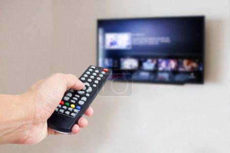 Photo pour Télécommande avec téléviseur au mur - image libre de droit