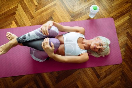 Photo for A beautiful fit blonde woman stretching out on her yoga mat. - Royalty Free Image