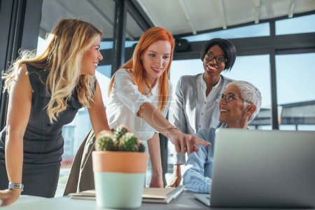 Photo pour Équipe de femmes d'affaires travaillant sur un ordinateur portable dans un café . - image libre de droit