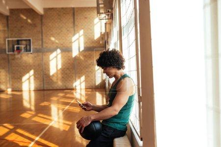 Photo pour Beau joueur de basket tenant la balle et utilisant un téléphone mobile . - image libre de droit