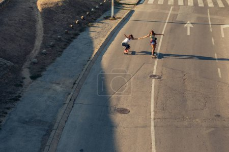 Photo for Two friends having fun riding skateboards outdoors. - Royalty Free Image