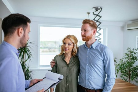 Photo pour Conseiller financier expliquant les détails de la nouvelle maison au jeune couple . - image libre de droit