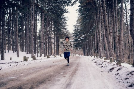 Full length portrait of a determined athlete man running in the winter.
