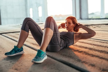 Photo for A young athletic woman doing sit ups in an urban area. - Royalty Free Image