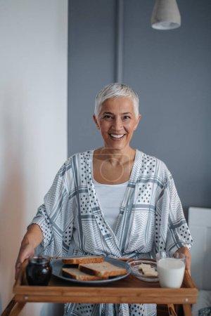 Porträt einer Seniorin beim Frühstück im Schlafzimmer.