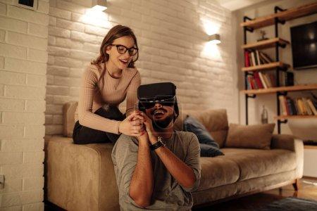 Foto de Joven pareja teniendo diversión con aparato de realidad virtual - Imagen libre de derechos