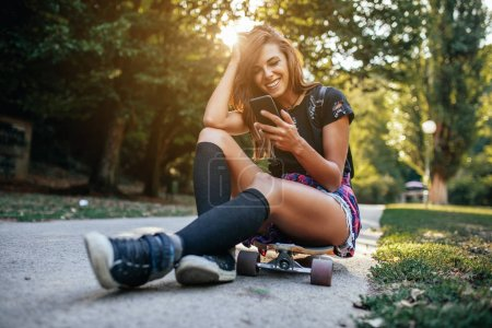 Photo for Young girl sitting on a long board , holding a mobile phone - Royalty Free Image