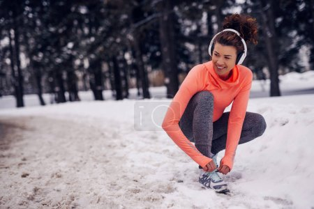 Young sportswoman lacing her shoes on a winter day