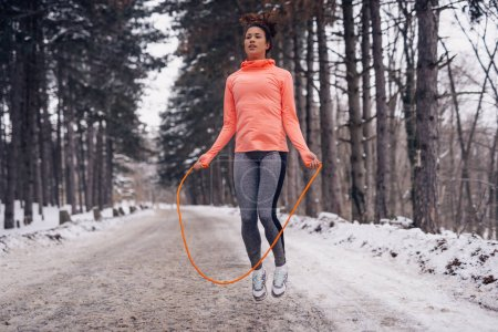 Young woman training with a skipping rope