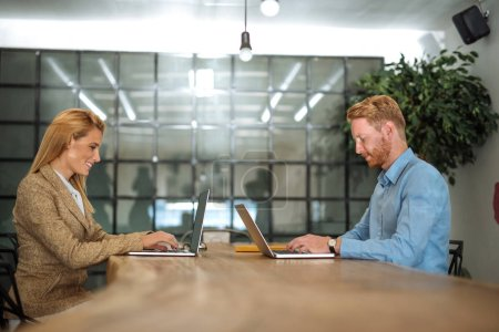 Photo for Shot of two business people working on their laptop computers - Royalty Free Image