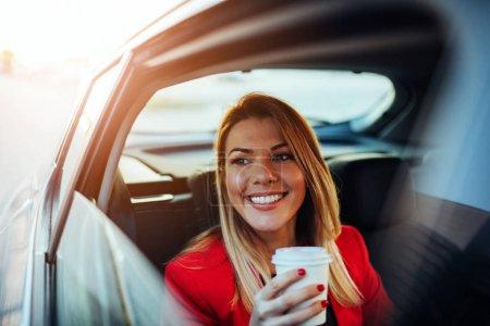 Photo pour Jeune femme d'affaires dans une voiture tenant une tasse de papier - image libre de droit