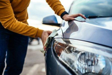 Photo pour Tourné d'un homme polissant sa voiture avec un chiffon en microfibre . - image libre de droit