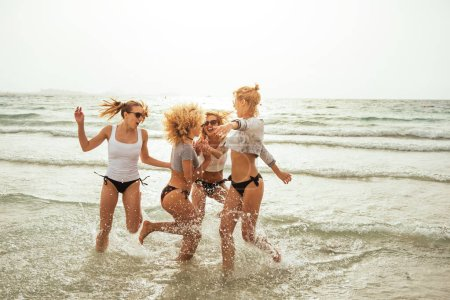 Photo for Happy girls holding hands and running on the beach. - Royalty Free Image