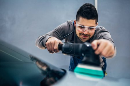 Man doing a car polish with a machine.