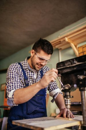 Photo for Young carpenter working on a machine in his workshop. - Royalty Free Image