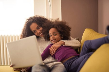 Photo for Mother and daughter playing on a computer indoors. - Royalty Free Image
