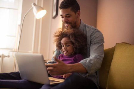 Portrait of a happy black dad showing his daughter how to use computer while she is sitting in his lap indoors.