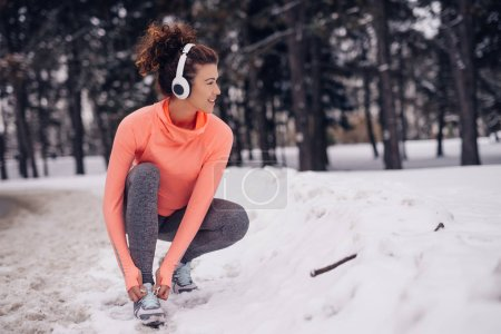 Portrait of a smiling athletic young woman tying her shoelaces in snow in the woods.